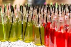 Variété de soudes dans des bouteilles en verre ouvertes avec des pailles Photographie stock libre de droits