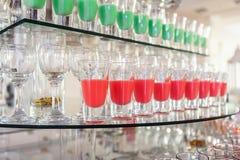 Variété de tirs verts et rouges colorés d'alcool en petits verres se tenant dans la rangée sur un support en verre images libres de droits