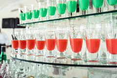 Variété de tirs verts et rouges colorés d'alcool en petits verres se tenant dans la rangée sur un support en verre image libre de droits