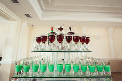 Variété de tirs verts et rouges colorés d'alcool en petits verres se tenant dans la rangée sur un support en verre photos stock