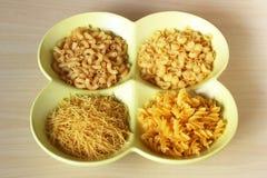 Variété sèche de pâtes dans les formes dans la cuvette sur la table Images stock