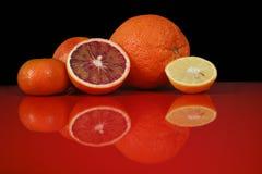 Vari agrumi freschi sul piano d'appoggio rosso con la riflessione e Immagine Stock
