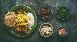 Vari alimenti indiani in ciotole su fondo rustico scuro fotografia stock
