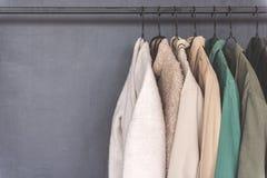 Vari cappotti sugli scaffali del metallo Immagini Stock