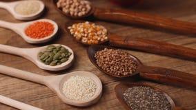 Vari cereali ed in cucchiai di legno sulla tavola stock footage