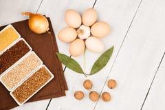 Vari chicchi in ciotole, uova, foglia di alloro, tavola-tovagliolo presentato sotto forma del fiore sulla tavola di legno bianca Fotografia Stock Libera da Diritti