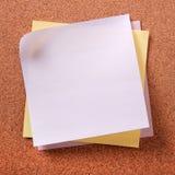 Vari colori parecchie note in calce appiccicose sul fondo del sughero Fotografia Stock