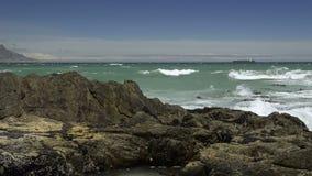 Vari colpi delle onde che si rompono davanti alla montagna della Tabella video d archivio