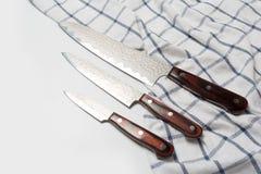 Vari coltelli da cucina utilizzati di acciaio inossidabile con le maniglie di legno marroni immagine stock