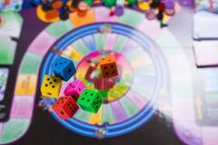 Vari dadi di colore di rotolamento cadono su una tavola con il gioco da tavolo Momenti di gioco nella dinamica Fotografie Stock Libere da Diritti