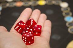 Vari dadi rossi di rotolamento cadono su una tavola con il gioco da tavolo Momenti di Gameplay Fotografia Stock Libera da Diritti