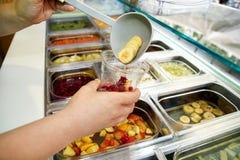Vari elementi sani della barra di insalata della verdura e della frutta fresca La mano sta preparando i frutti per il frullato or Fotografia Stock Libera da Diritti