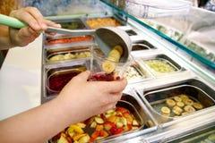 Vari elementi sani della barra di insalata della verdura e della frutta fresca La mano sta preparando i frutti per il frullato or Immagini Stock