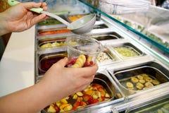 Vari elementi sani della barra di insalata della verdura e della frutta fresca La mano sta preparando i frutti per il frullato or Immagine Stock