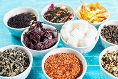 Vari erbe e tè medicinali secchi in parecchie ciotole su fondo di legno blu Fotografia Stock
