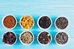 Vari erbe e tè medicinali secchi in parecchie ciotole su fondo di legno blu da sopra Immagine Stock