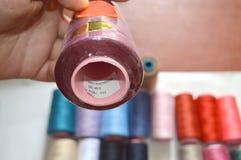 Vari fili colorati con i bottoni dei vestiti su fondo bianco immagini stock libere da diritti