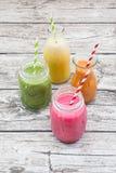 Vari frullati variopinti della frutta in bottiglie di vetro Fotografia Stock Libera da Diritti