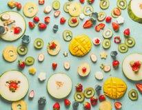 Vari frutti e bacche affettati su fondo blu-chiaro, vista superiore, disposizione del piano Alimento sano di estate fotografia stock libera da diritti