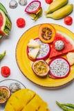 Vari frutti tropicali sul piatto giallo su fondo bianco, vista superiore fotografia stock