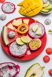 Vari frutti tropicali sul piatto rosso su fondo bianco, vista superiore fotografie stock