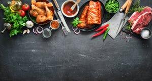 Vari generi di griglia e di carni del bbq con gli utensili d'annata del macellaio e della cucina immagini stock