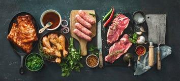 Vari generi di griglia e di carni del bbq con gli utensili d'annata del macellaio e della cucina fotografie stock
