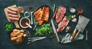 Vari generi di griglia e di carni del bbq con gli utensili d'annata del macellaio e della cucina fotografia stock libera da diritti