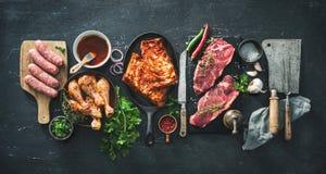 Vari generi di griglia e di carni del bbq con gli utensili d'annata del macellaio e della cucina immagini stock libere da diritti