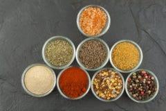 Vari generi di spezie in ciotole di vetro su un fondo dell'ardesia Immagine Stock