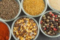 Vari generi di spezie in ciotole di vetro su un fondo dell'ardesia Fotografia Stock Libera da Diritti