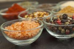 Vari generi di spezie in ciotole di vetro su un fondo dell'ardesia Fotografia Stock