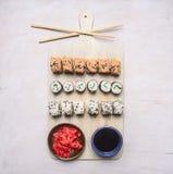 Vari generi di sushi su un tagliere con il tagliere bianco della salsa dei bastoncini, dello zenzero e di soia, vista superiore Immagine Stock Libera da Diritti