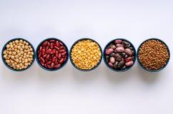 Vari legumi Lenticchie, ceci, piselli e fagioli in ciotole blu su un fondo bianco Vista superiore fotografia stock