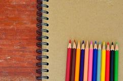 Vari matite di colore e taccuino Fotografie Stock