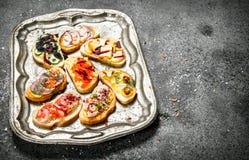 Vari panini con il caviale, il bacon, il formaggio e gli ortaggi freschi rossi su un vassoio d'acciaio Fotografie Stock