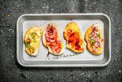 Vari panini con il caviale, il bacon, il formaggio e gli ortaggi freschi rossi su un vassoio d'acciaio Fotografia Stock