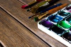 Vari pennelli e pittura sulla vecchia tavola di legno prescelto fotografie stock