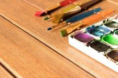 Vari pennelli e pittura sulla vecchia tavola di legno prescelto immagine stock