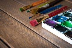 Vari pennelli e pittura sulla vecchia tavola di legno prescelto fotografia stock libera da diritti