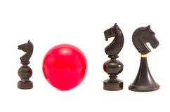 Vari pezzi degli scacchi neri del cavallo e palla di biliardo rossa isolati Fotografia Stock
