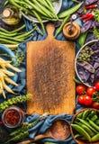 Vari piselli e fagioli variopinti dei baccelli con la cottura degli ingredienti intorno al tagliere vuoto, su fondo blu rustico s fotografie stock