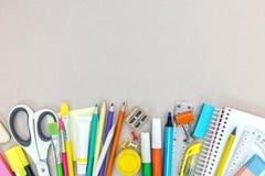 Vari rifornimenti ed ufficio di scuola stazionari su fondo grigio Fotografia Stock