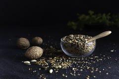 Vari semi in una ciotola di vetro su fondo scuro fotografia stock