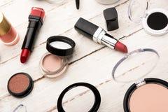 Vari spazzole e cosmetici per l'applicazione del trucco sulla tavola Fotografia Stock