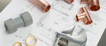 Vari strumenti degli idraulici e materiali dell'impianto idraulico sulla P architettonica Fotografia Stock
