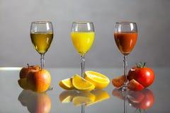 Vari succo e frutta su una tavola di vetro Fotografie Stock