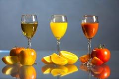 Vari succo e frutta su una tavola di vetro Fotografia Stock Libera da Diritti