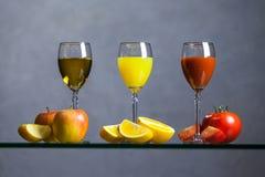 Vari succo e frutta su una tavola di vetro Immagini Stock
