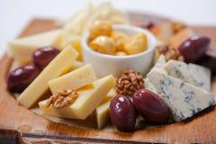 Vari tipi di formaggi su un bordo di legno Immagini Stock